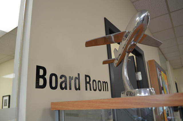 The entry to a Board Room in the Canadian Tourism College with a small air plane statue outside.