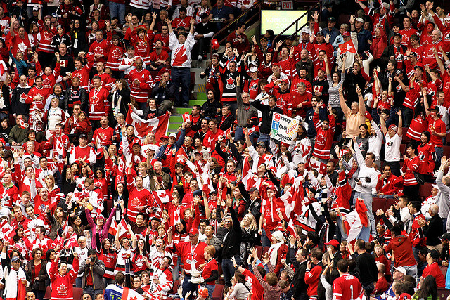 A crowd of people dressed in red and white Canadian jerseys cheer.