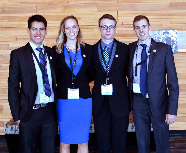 Four students dressed in formal business attire.