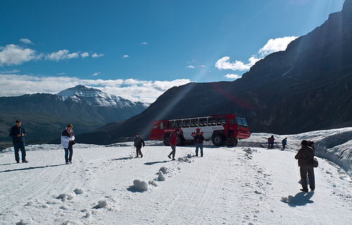 People walk aross the snow with their bus parked behind them.