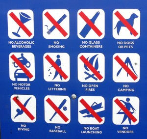 A sign listing things that are not allowed like pets, alcohol, baseball, open fires and more.