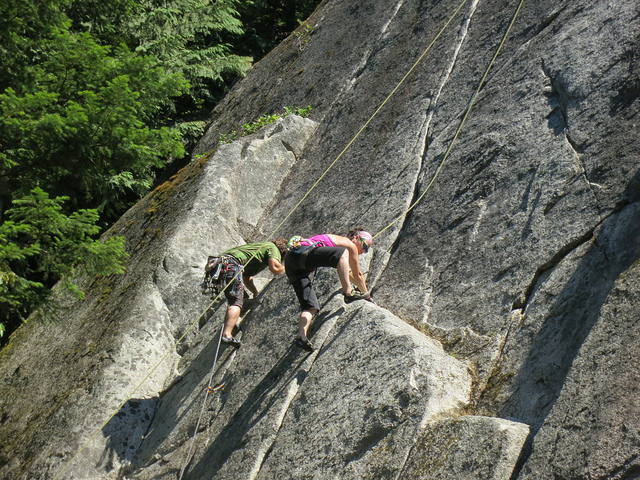 Two people climb a rock face.