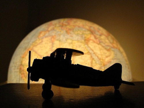 A toy plane in front of a globe.