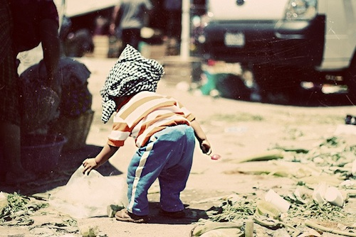 A small child with cloth wrapped around its head plays with debris in the street.