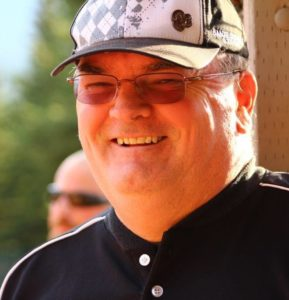 A man in a baseball cap and sunglasses smiles outside.