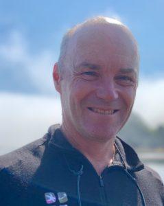 A balding man in a fleece jacket smiles in bright sunlight.