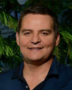 A man in a polo shirt smiles in front of a coniferous tree.