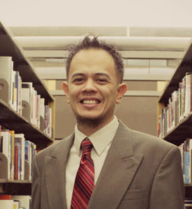A man in a suit and tie smiles in between bookshelves in a library.