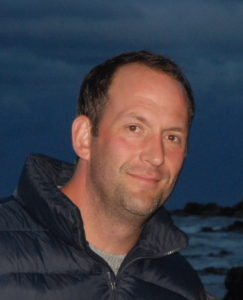 A man in a puffy jacket smiles by the ocean in the evening.