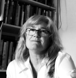 Black-and-white photo of a woman in a blouse and glasses smiling in front of a bookcase.