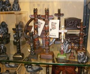 Small mass-produced totem poles on a shop shelf.