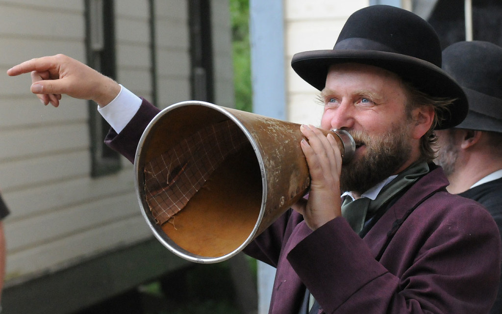 A man dressed in a Victorian suit and bowler hat, speaking into a megaphone.