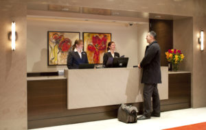 Two female front desk employees speak to a male guest in a hotel lobby.