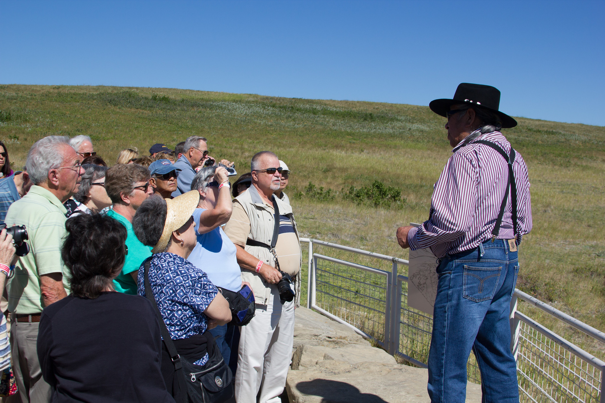 Tourists gather around a man wearing a cowboy hat next to a short metal fence in front of a plain.