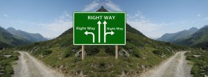 Two roads dissected by a hill and a sign pointing in four different directions, each labeled as the right way