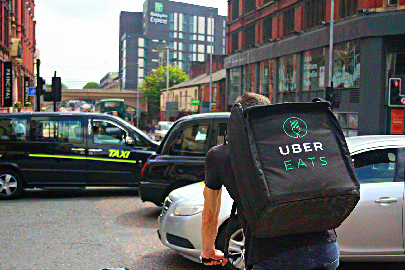 A photo shows the rear view of an Uber Eats' food delivery driver with a backpack, cycling along a busy Oxford Road in Manchester, England.