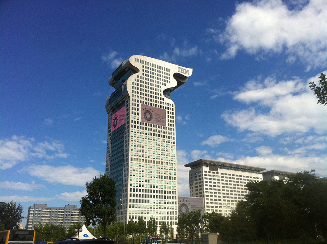 A photo shows a view of the Dragon Building, I B M's headquarters based in China, against a clear blue sky.