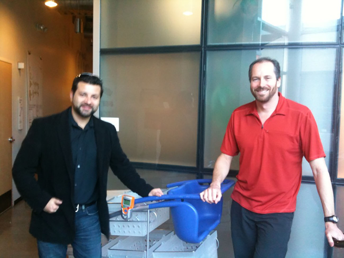 A photo shows two IDEO male representatives posing for the camera with a model of the new shopping cart introduced by IDEO.
