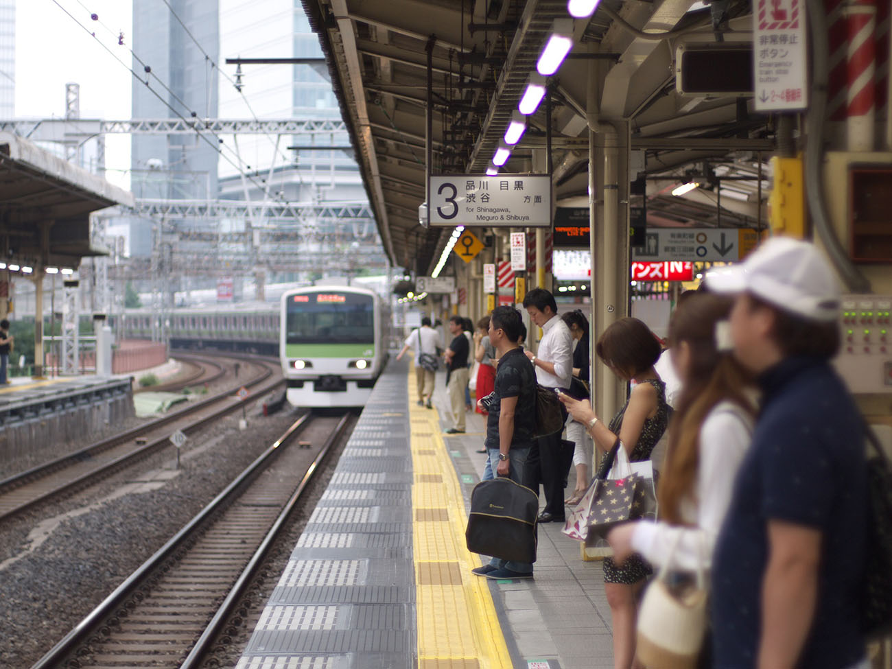 A photo shows passengers waiting while a train enters the platform at a railway station in Japan.