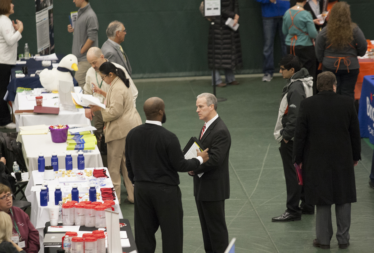 A photo shows recruiters speaking with potential employees and job seekers at a job fair at the College of DuPage.