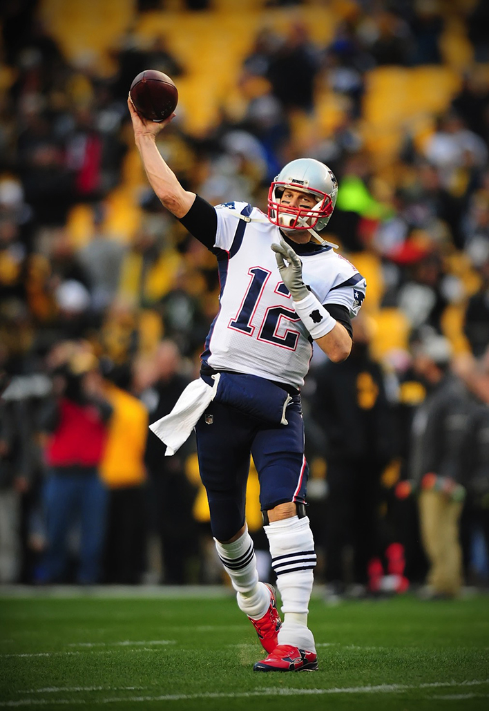 A photograph of Tom Brady in a field throwing a pass.