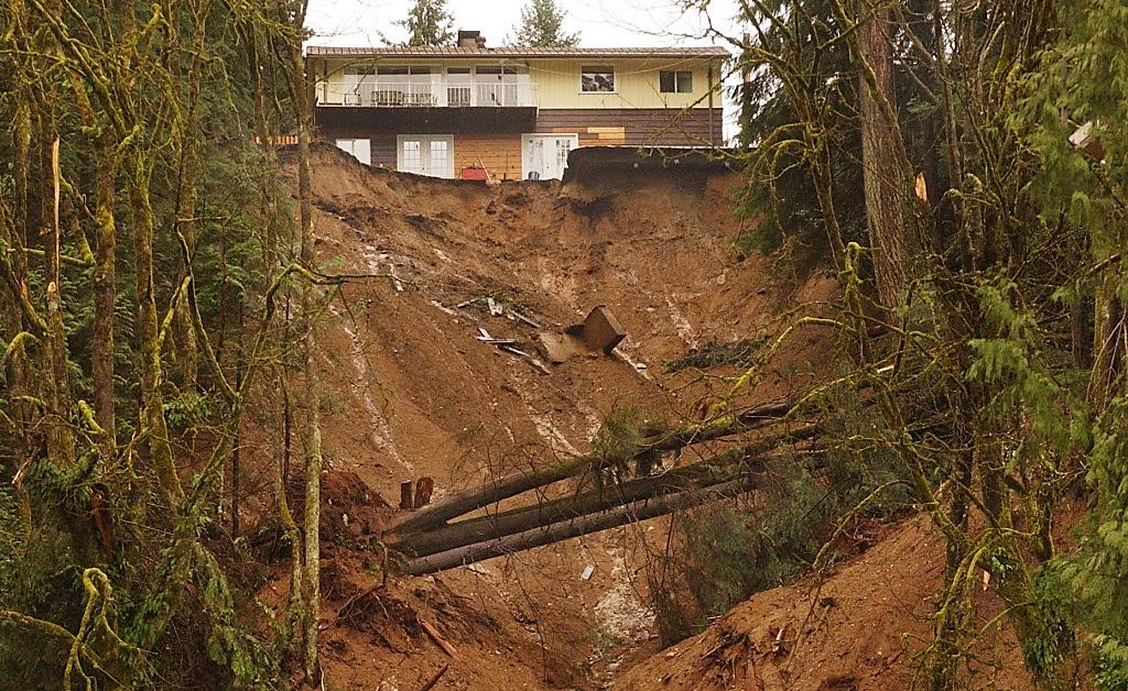 A steep, muddy cliff at the end of a residential yard where the embankment gave way