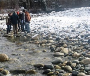 A group of people peer down at rocks in a stream
