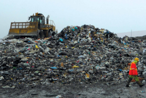 A pile of garbage at a landfill and a large bulldozer in the background