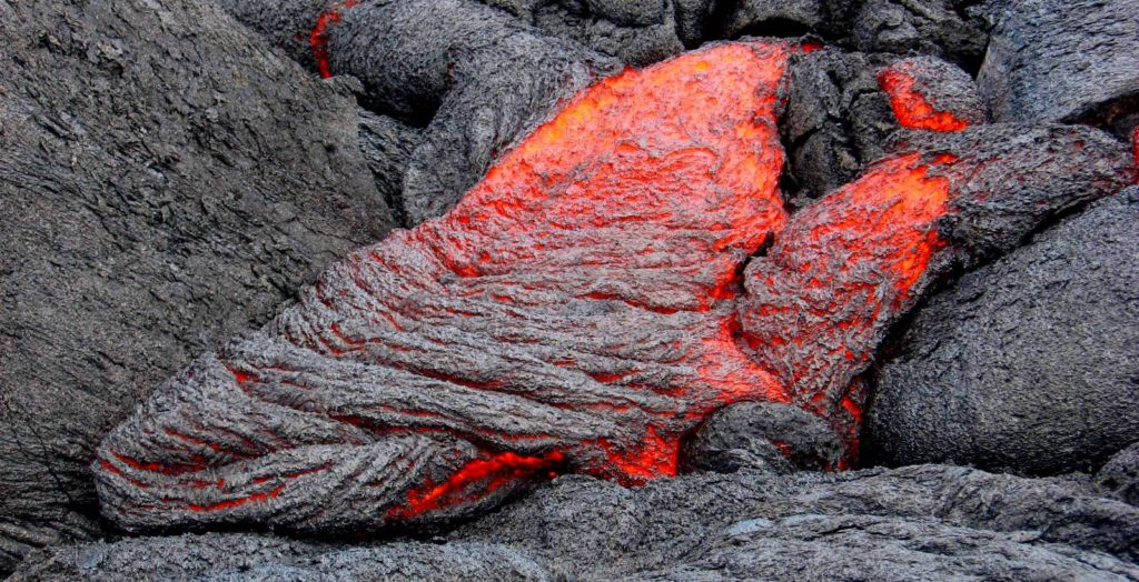 Red hto magma runs down rocks