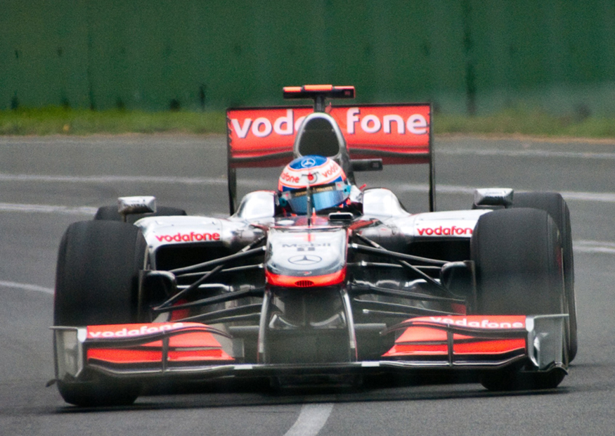 The figure shows, from front, a red and silver coloured Formula One car turning through a curve in a race on the Melbourne Grand Prix track, with the driver in seat.
