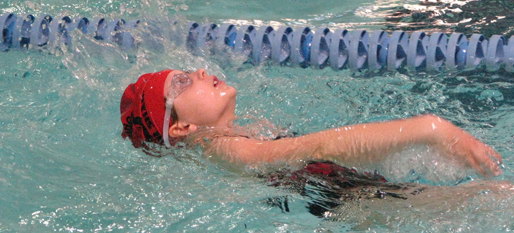 A swimmer in a pool doing the backstroke.