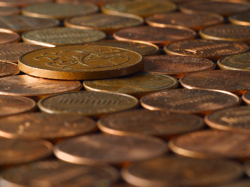 Photograph of many coins laid down on a surface, some with heads shown up and some with tails shown up.