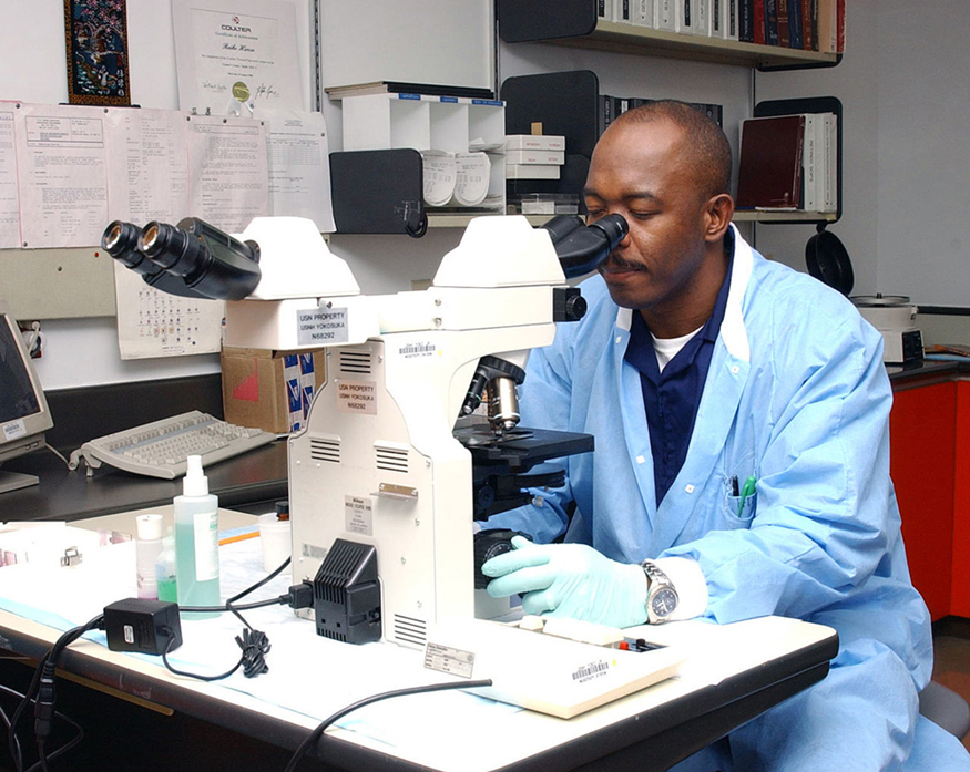 Image of a man viewing through the ocular lens and with his hand on the fine adjustment of the microscope.
