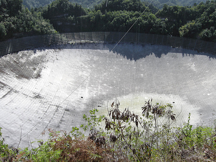 The figure shows a photograph from above looking into the Arecibo Telescope in Puerto Rico. It is a huge bowl-shaped structure lined with reflecting material. The diameter of the bowl is three times as long as a football field. Trees can be seen around the bowl, but they do not shade the bowl significantly.