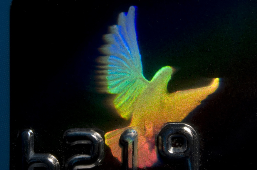 The image shows a rainbow-colored hologram of a bird on a credit card.