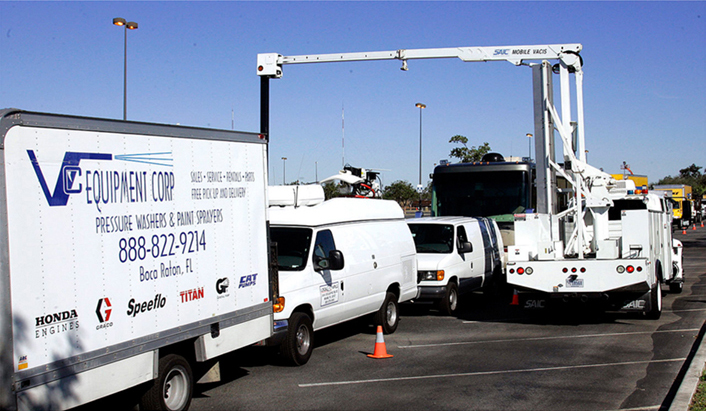 Vehicles being inspected by another vehicle with a boom-type x-ray scanner attached to it.