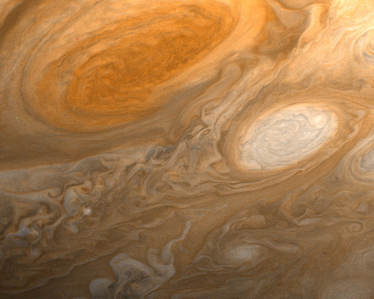 The picture shows what looks like a flowing orangish liquid into which some milk has been mixed. The main features are two eddies or vortices: a larger one that is a darker orange than the background and the other, smaller one, that is more milky than the background.