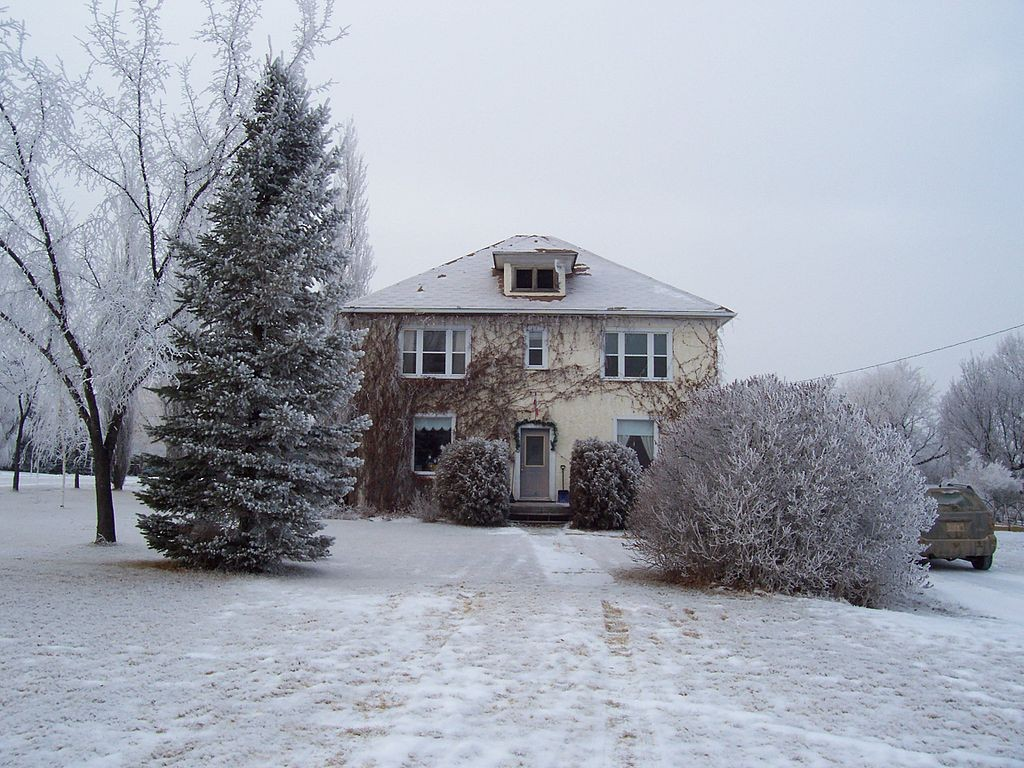 Two-story period home in a frosty field with frosty foliage.