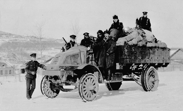Seven men pose on top of and beside a military truck loaded with supplies.