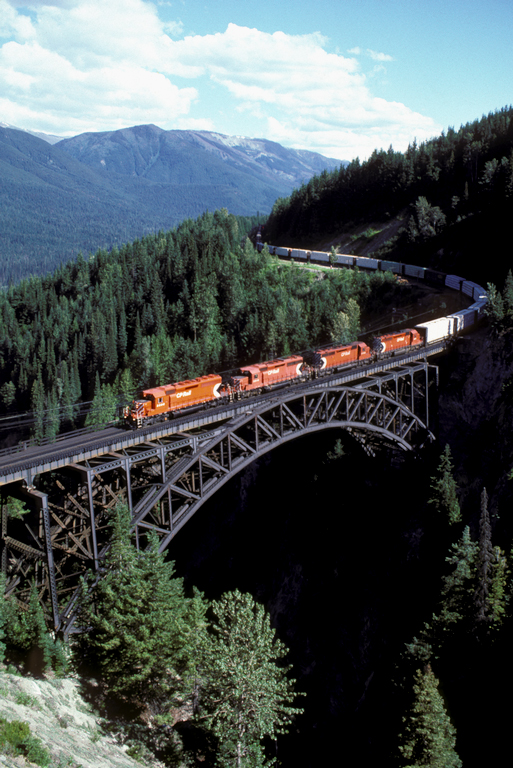 A train crosses a bridge in the mountains.