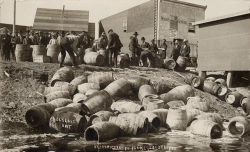 Barrels are scattered all over the ground. Men in suits look on.