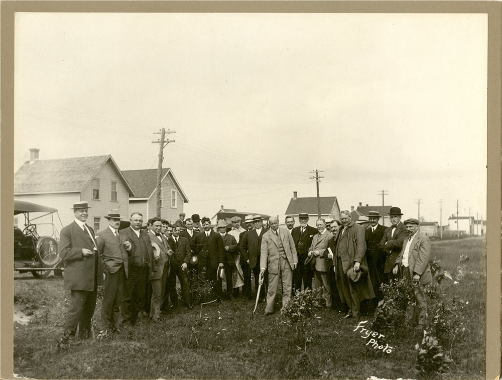 Two dozen men pose in suits, with one in the centre holding a shovel in the ground.