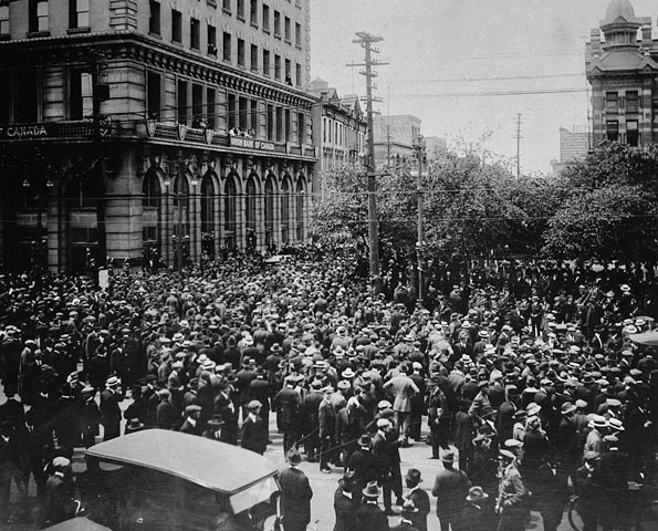 A city street packed with men. A car is in the foreground.