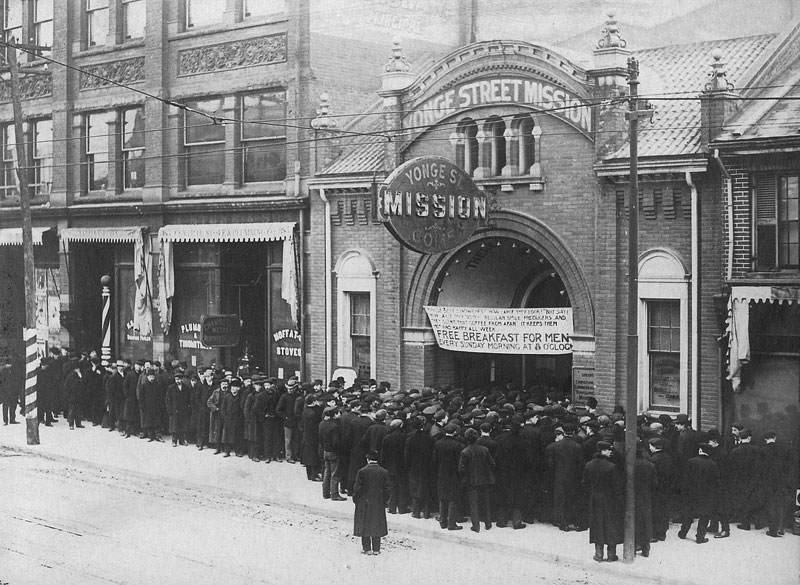 "Men crowd outside a building with a sign ""Free breakfast for men every Sunday morning at 8 o'clock."""