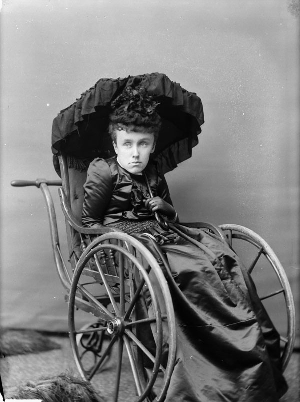 A woman in a dark dress holds a black umbrella and sits in a wheelchair.