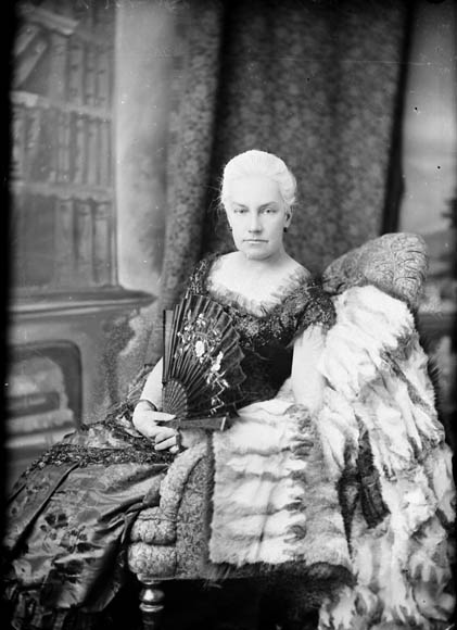A woman wearing a Victorian gown sits in an opulent armchair, fanning herself.