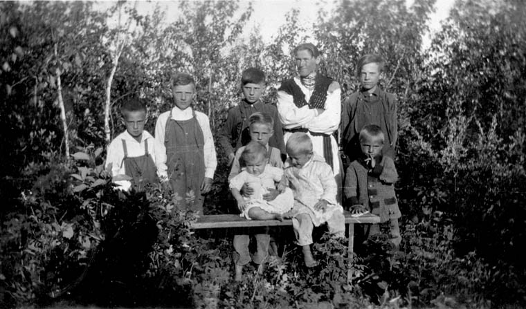 A woman poses with eight children (mostly boys) in front of a stand of bushes.