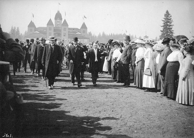 Dignitaries walking past a large crowd. An ornate building is in the background.