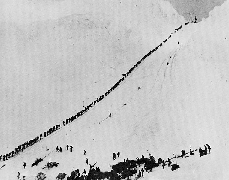 A long line of people ascend a snowy mountain pass.