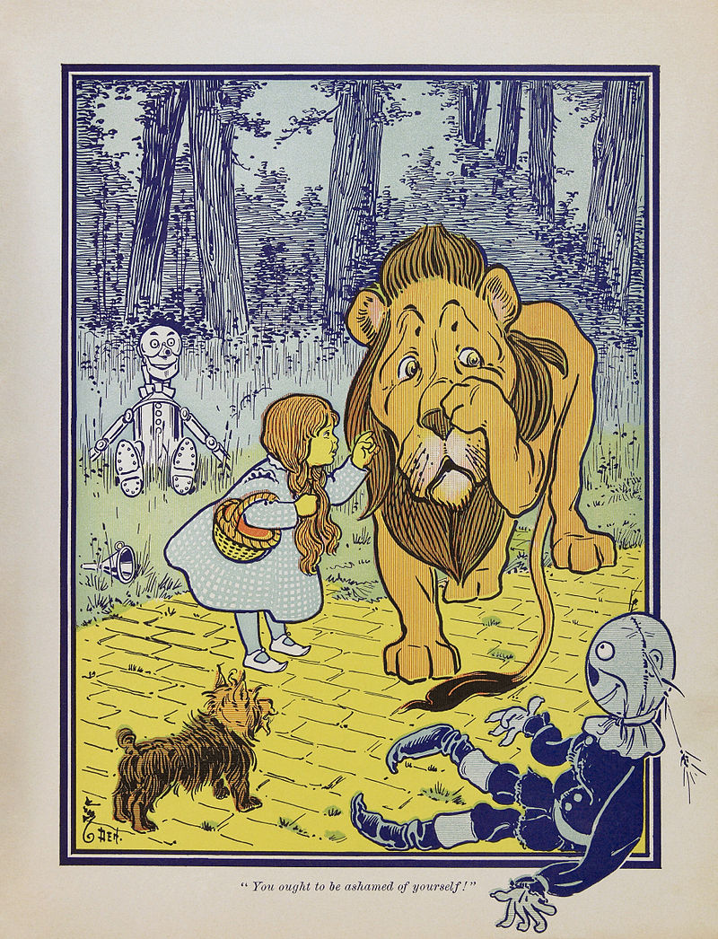 A girl reaches for a lion, who puts his paw on his face, distraught. A scarecrow and terrier watch.